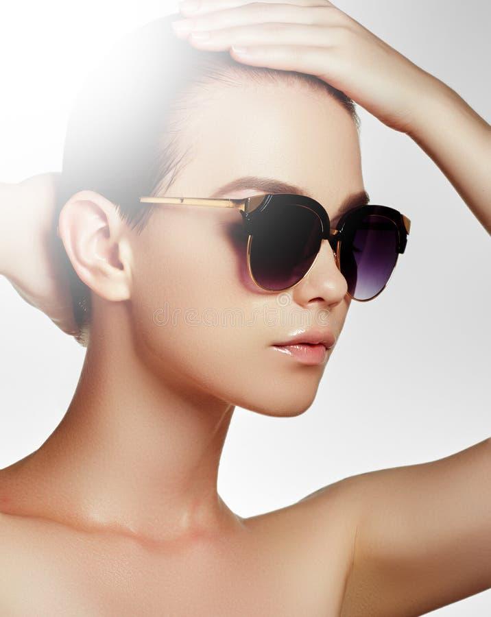 时尚太阳镜 泳装的性感的妇女有金黄太阳镜和自然构成的 魅力射击了一个美好的模型 免版税图库摄影