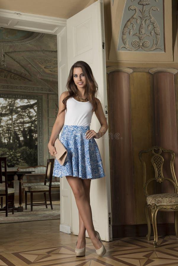 时尚女孩在古色古香的宫殿 免版税库存照片
