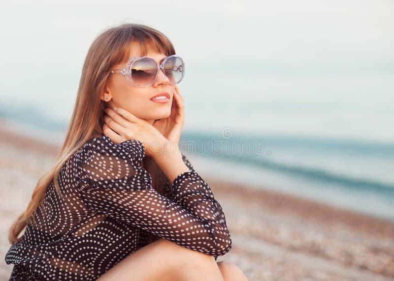 时尚女孩坐海滩 免版税库存图片