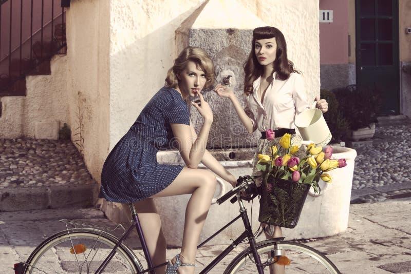 时尚女孩夫妇有自行车的 库存照片