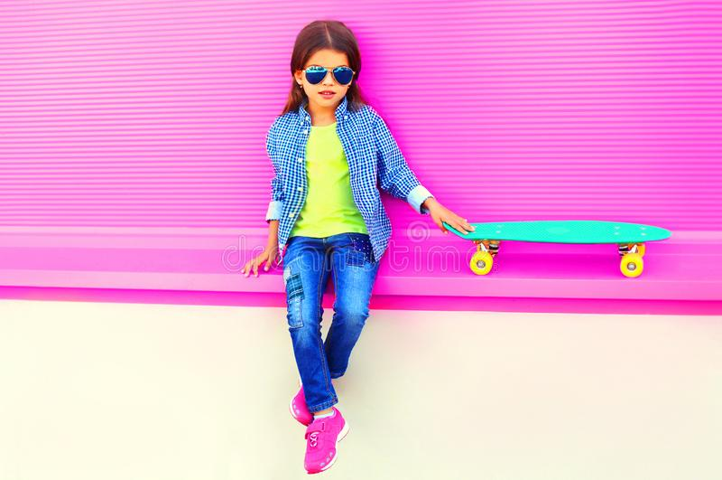 时尚女孩孩子与滑板在城市坐五颜六色的桃红色墙壁 免版税库存图片