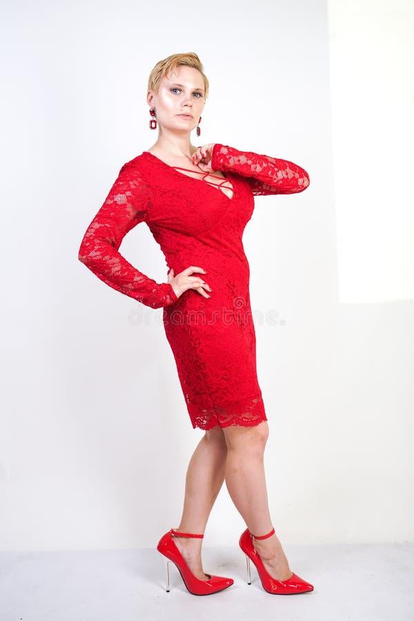 时尚女性在单独红色鞋带礼服身分 正有短发的大小白肤金发的妇女和摆在平衡的胖的身体中间l 免版税库存照片
