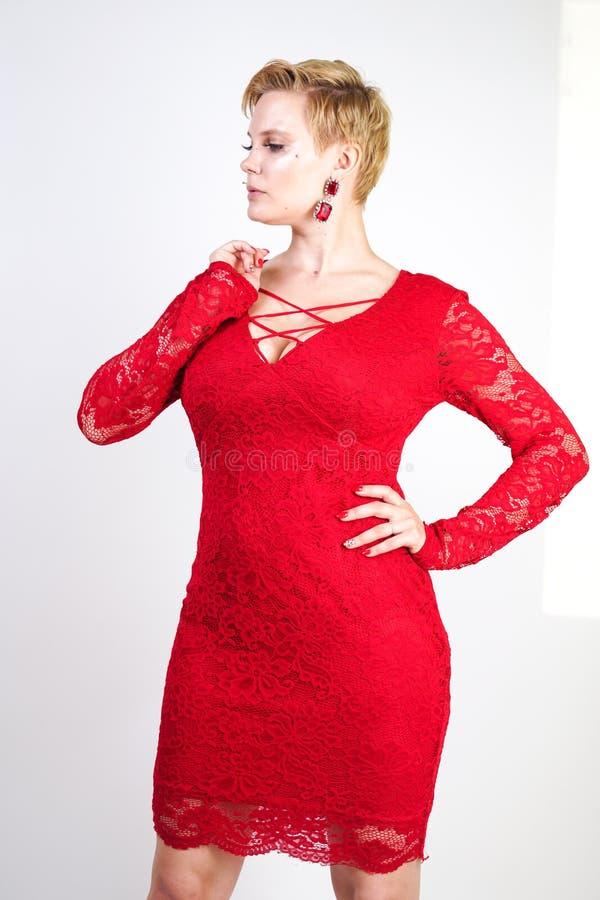 时尚女性在单独红色鞋带礼服身分 正有短发的大小白肤金发的妇女和摆在平衡的胖的身体中间l 图库摄影