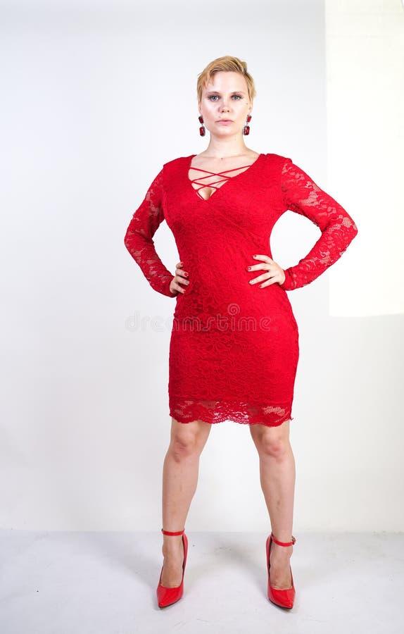时尚女性在单独红色鞋带礼服身分 正有短发的大小白肤金发的妇女和摆在平衡的胖的身体中间l 库存照片
