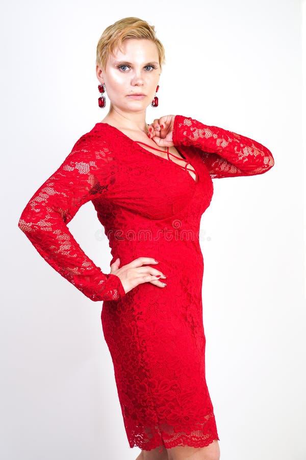 时尚女性在单独红色鞋带礼服身分 正有短发的大小白肤金发的妇女和摆在平衡的胖的身体中间l 免版税库存图片