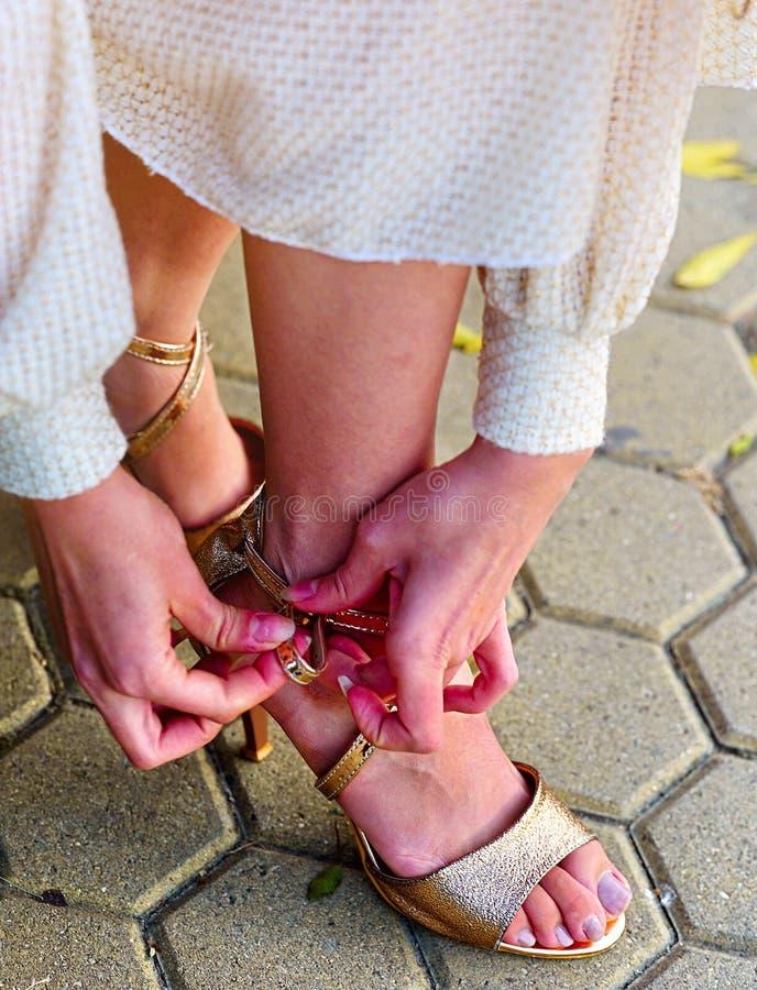 时尚妇女秋天在鞋子上把放的春天礼服在长凳 免版税库存照片