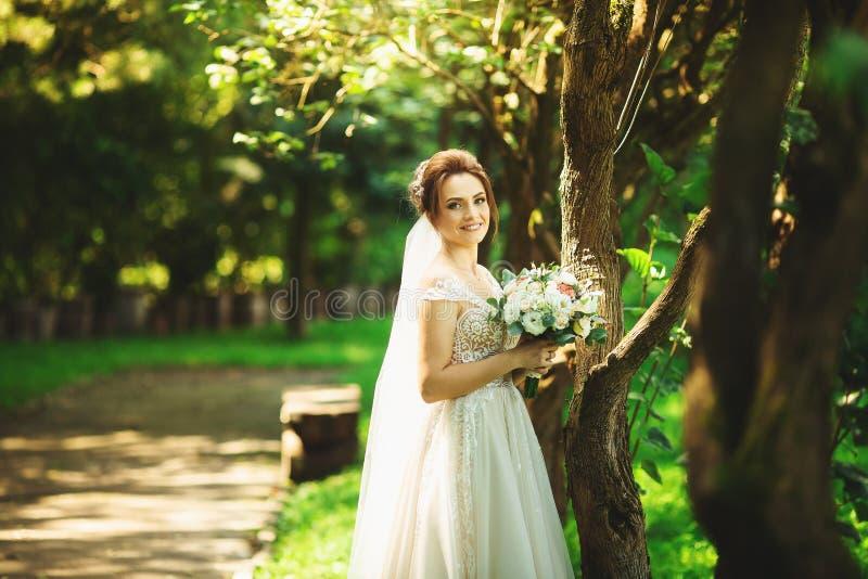时尚婚纱的新娘在自然本底 E 免版税库存照片