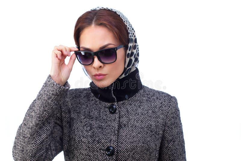 时尚少妇穿太阳镜和外套 免版税库存图片