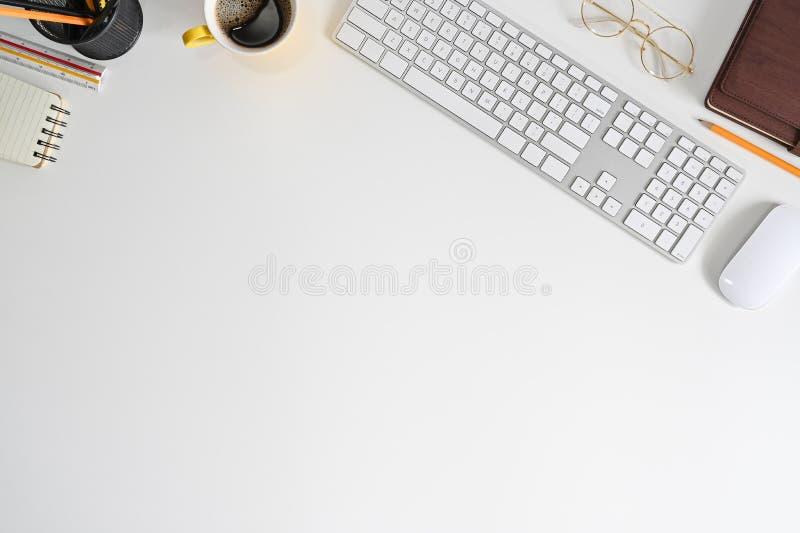 时尚工作场所的办公桌顶视图桌、电脑键盘、咖啡和笔记本 免版税库存照片