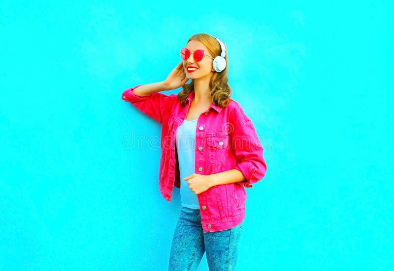 时尚微笑的妇女听到在无线耳机的音乐在蓝色的桃红色牛仔布夹克 免版税库存图片