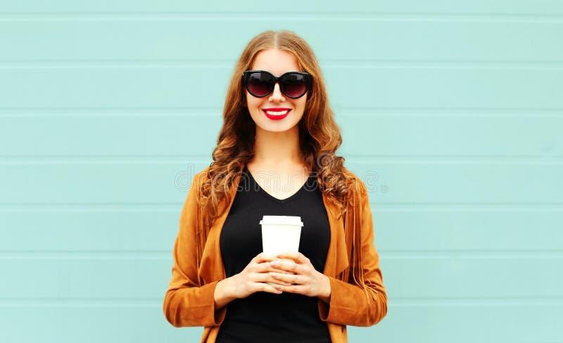 时尚微笑的妇女拿着在太阳镜的咖啡杯在灰色 免版税库存图片