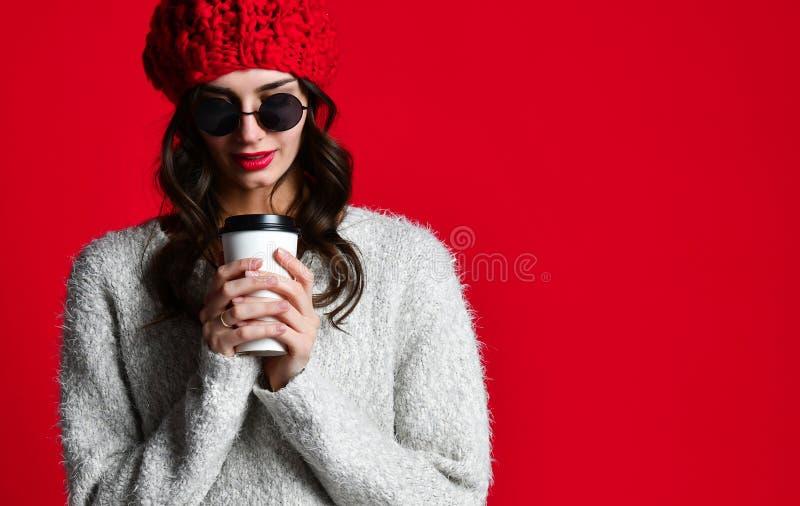 时尚愉快的微笑的妇女拿着在红色墙壁背景的咖啡杯 免版税库存照片