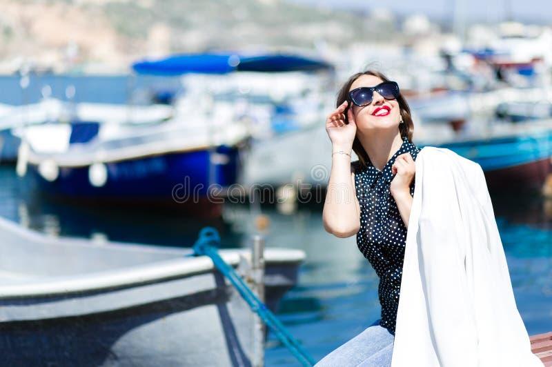 时尚时髦美丽的笑的妇女whilte成套装备摆在海洋小船背景的太阳镜的 库存照片