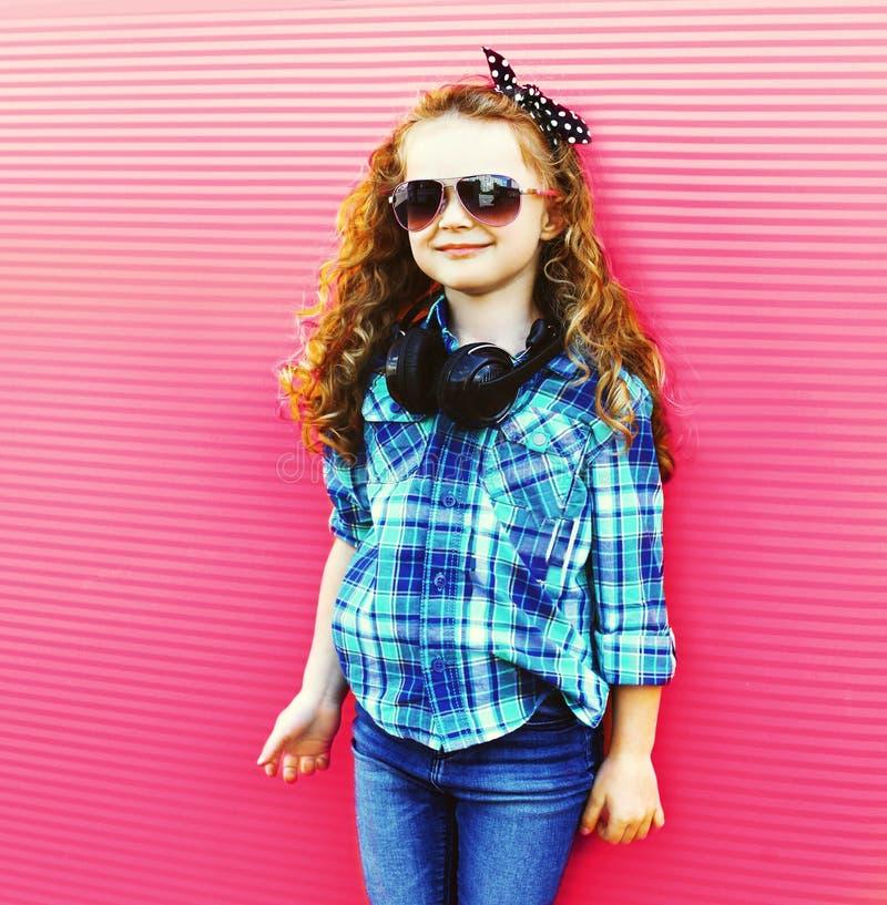 时尚有无线耳机的女孩孩子在五颜六色的桃红色墙壁上 免版税库存照片