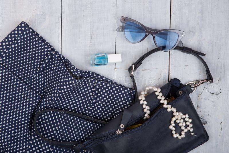 时尚材料-袋子,长裤,太阳镜,指甲油,在白色木背景的珍珠首饰 免版税库存照片