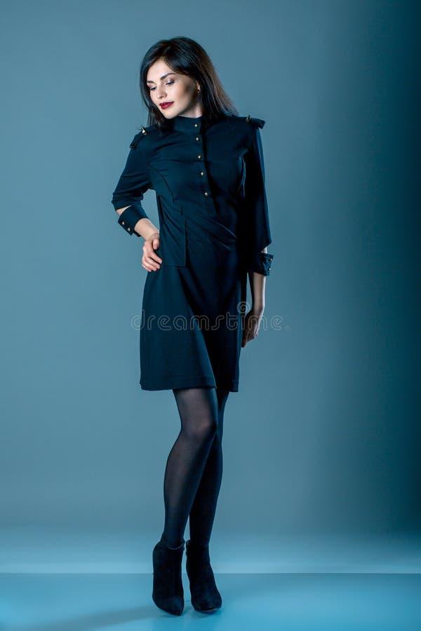 时尚样式妇女完善的身体形状深色的头发穿戴黑色大礼服高雅偶然美丽的式样秘书空中小姐d 库存照片