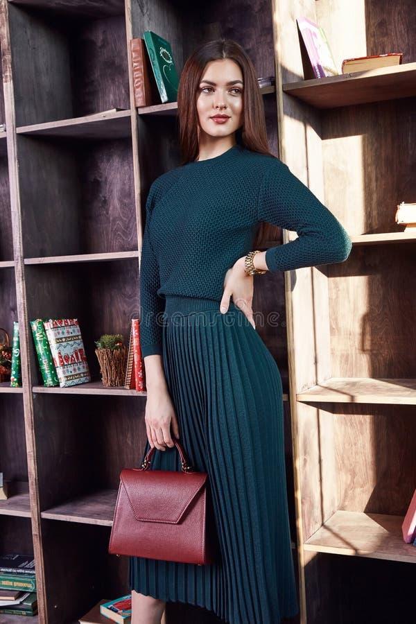 时尚样式妇女完善的身体形状深色的头发穿戴绿色羊毛大礼服高雅偶然美好的式样秘书空气主人 库存图片