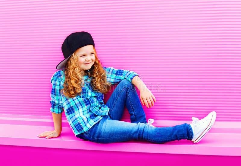 时尚棒球帽的儿童女孩有在五颜六色的桃红色墙壁上的卷发的 库存图片