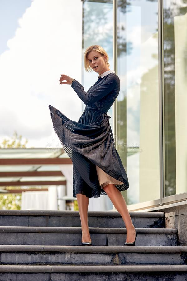 时尚概念经典之作 一年轻美女的画象在城市 在摆在照相机的一件长的夏天礼服的模型 免版税库存图片