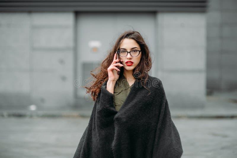 时尚概念:有长的头发、玻璃、红色嘴唇站立在现代墙壁附近的佩带在绿色衣服和灰色je的美丽的女孩 库存图片