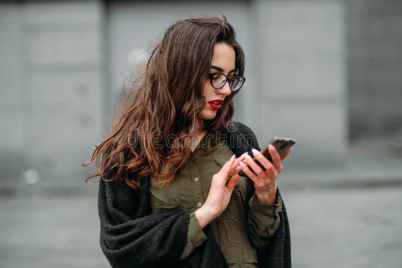 时尚概念:有长的头发、玻璃、红色嘴唇站立在现代墙壁附近的佩带在绿色衣服和灰色je的美丽的女孩 免版税库存图片