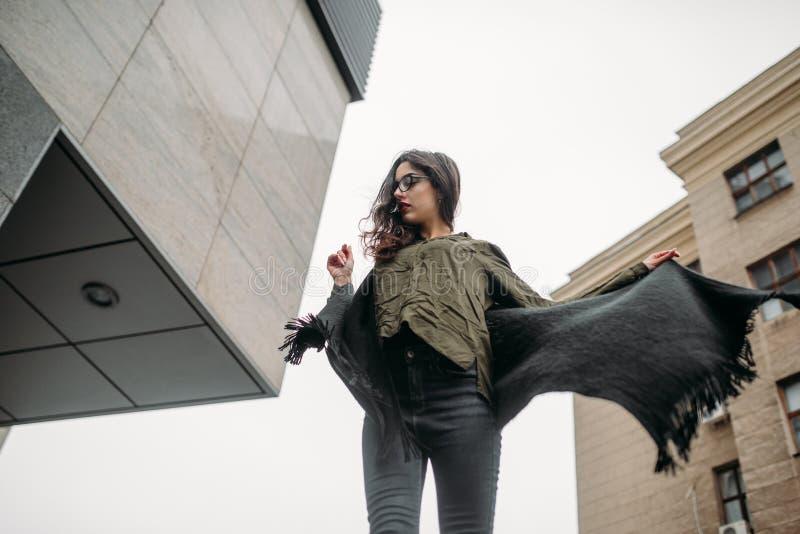 时尚概念:有长的头发、玻璃、红色嘴唇站立在现代墙壁附近的佩带在绿色衣服和灰色je的美丽的女孩 图库摄影