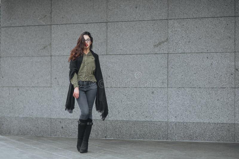 时尚概念:有长的头发、玻璃、红色嘴唇站立在现代墙壁附近的佩带在绿色衣服和灰色je的美丽的女孩 库存照片