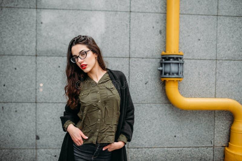 时尚概念:有长的头发、玻璃、红色嘴唇站立在现代墙壁附近的佩带在绿色衣服和灰色je的美丽的女孩 免版税库存照片