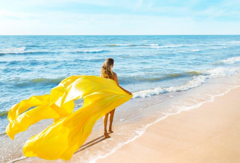 时尚模特穿黄色招摇裙走海滩,女人后视,丝布在风中摇动 库存照片