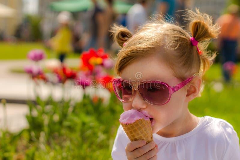 时尚玻璃的女孩吃着冰淇凌 孩子和可口冰淇凌 免版税库存图片