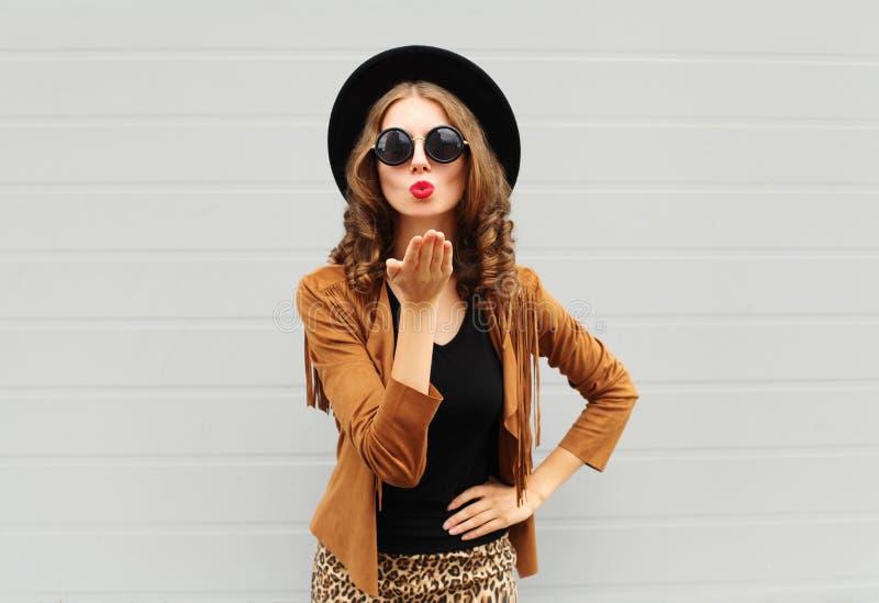 时尚生活方式画象妇女送空气穿一件黑帽会议、太阳镜和棕色夹克的甜亲吻户外在城市 库存图片