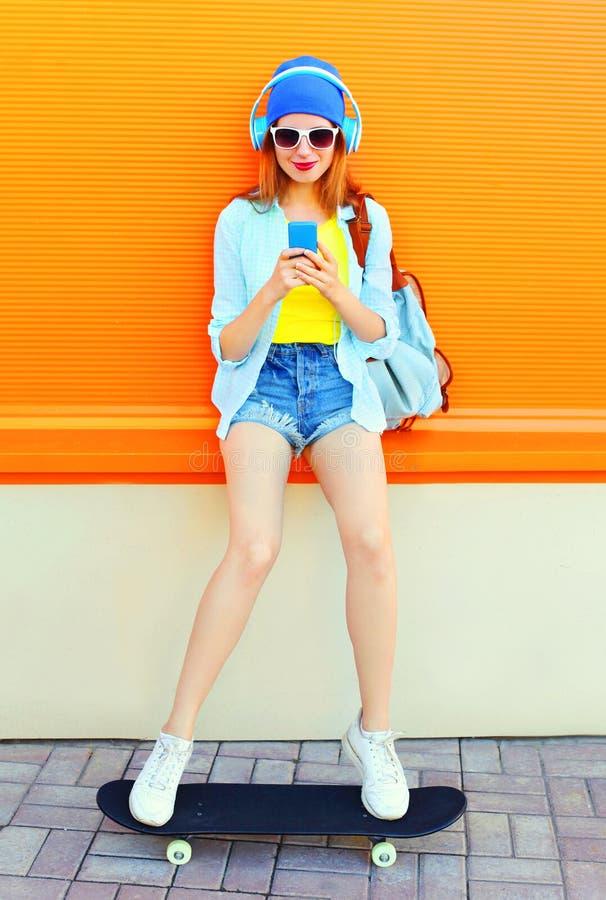时尚相当凉快的女孩是听到音乐,并且使用智能手机坐在五颜六色的桔子的一个滑板 免版税库存照片