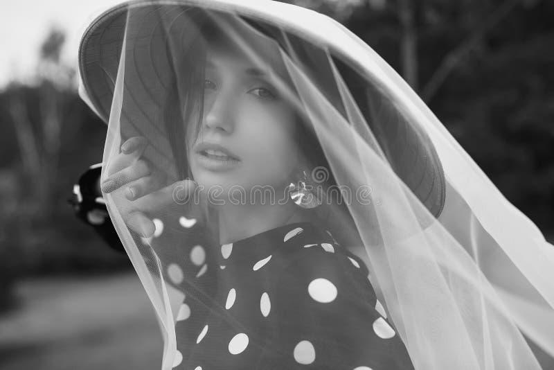 时尚礼服的华美的深色的妇女有秸杆中国人帽子的 图库摄影