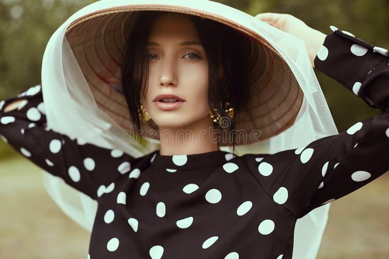 时尚礼服的华美的深色的妇女有秸杆中国人帽子的 免版税库存图片