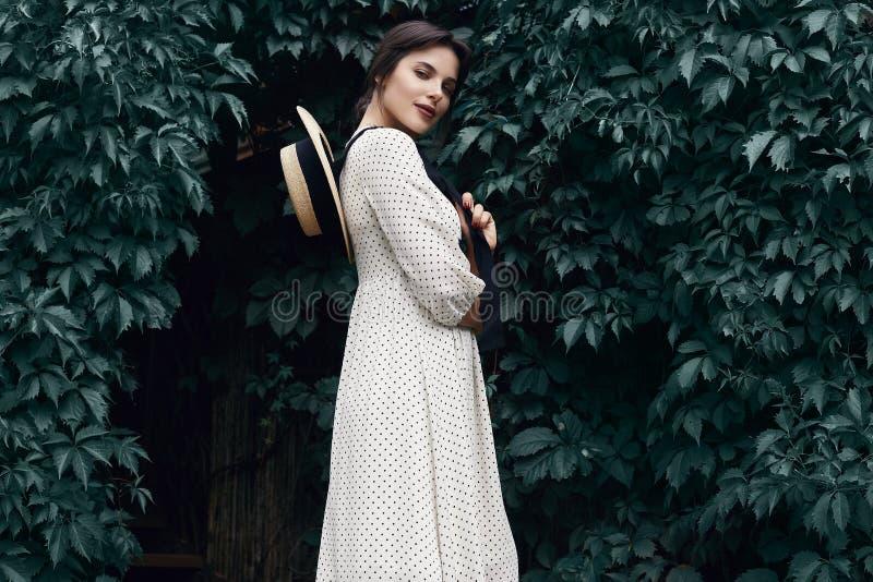 时尚礼服的华美的聪慧的深色的妇女有草帽的 免版税图库摄影