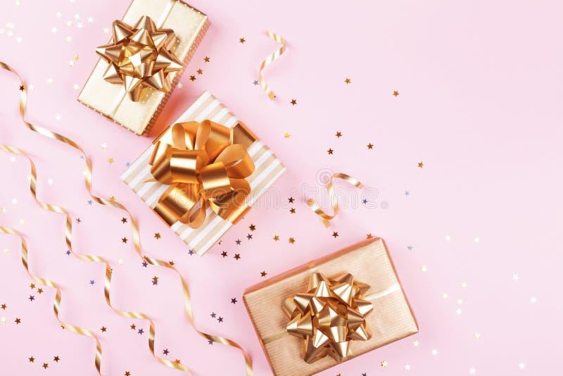 时尚礼物或当前箱子有金黄弓、蛇纹石和星五彩纸屑的在桃红色淡色台式视图 圣诞节舱内甲板位置 免版税库存照片