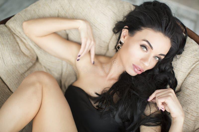 时尚秀丽美丽的深色的女孩趋向画象有长和发光的卷发的 生有娃娃脸的式样妇女 免版税库存照片