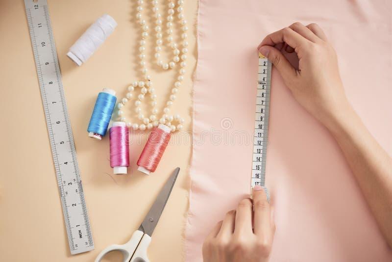 时尚编辑,摆在她的有被切开的织品的,在桌上的自由空间工作场所的妇女裁缝 服装业,剪裁概念 免版税库存照片