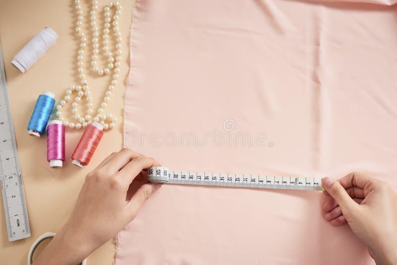 时尚编辑,摆在她的有被切开的织品的,在桌上的自由空间工作场所的妇女裁缝 服装业,剪裁概念 库存照片