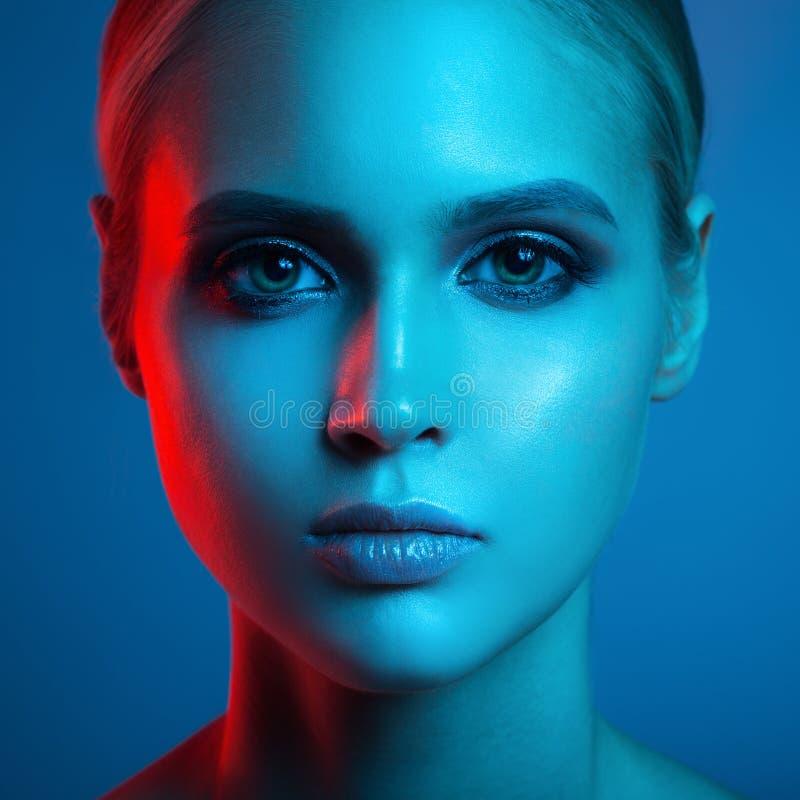 时尚美丽的妇女面孔艺术画象  红色和蓝色光 库存照片