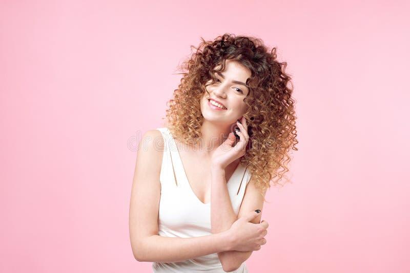 时尚美丽的微笑的妇女演播室画象有非洲的卷毛发型的被隔绝在桃红色背景 时尚和 库存图片
