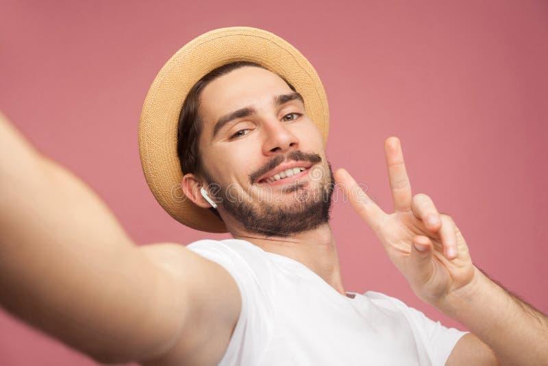 时尚英俊的有胡子的年轻行家博客作者接近的画象摆在和做selfie的白色衬衫和偶然帽子的  免版税图库摄影