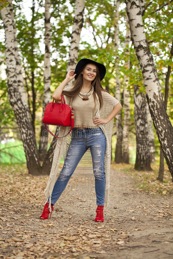 时尚蓝色牛仔裤和红色袋子的少妇走在秋天的 库存照片