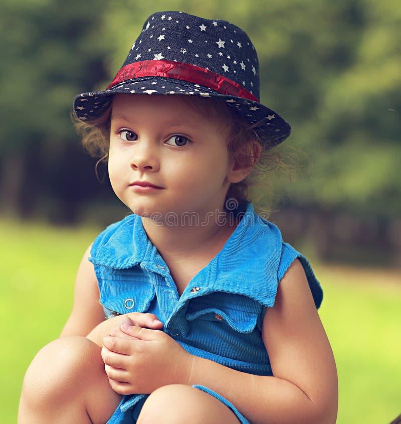 时尚蓝色牛仔裤的漂亮的孩子女孩穿戴坐 免版税库存图片
