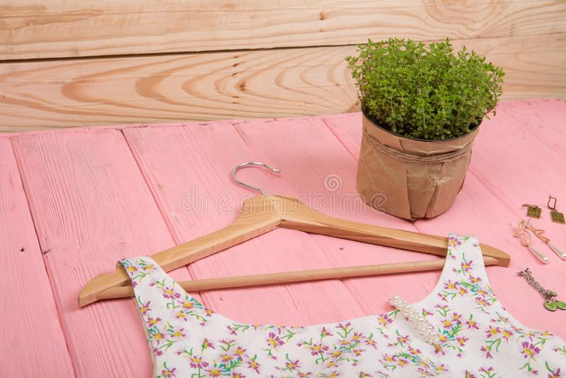 时尚趋向-在花卉图案的礼服在挂衣架和首饰垂悬在木背景 免版税图库摄影