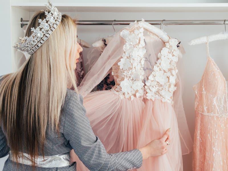 时尚选择晚礼服的陈列室夫人 免版税库存照片