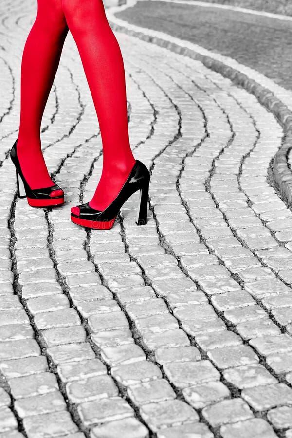 时尚都市妇女的腿,脚跟 黑白色,红色 免版税库存照片