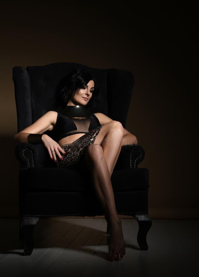 时尚黑内衣和豹子印刷品裙子的性感的夫人作梦与在她的嘴唇的轻微的微笑在大扶手椅子 库存图片