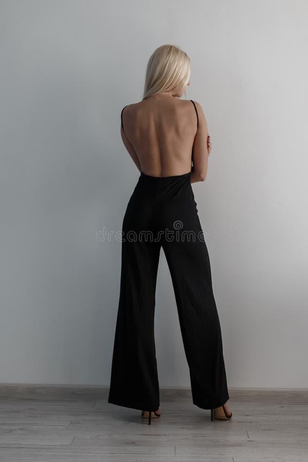 时尚黑礼服的时髦的美丽的年轻白肤金发的女孩有开背部的在白色墙壁附近站立 免版税图库摄影