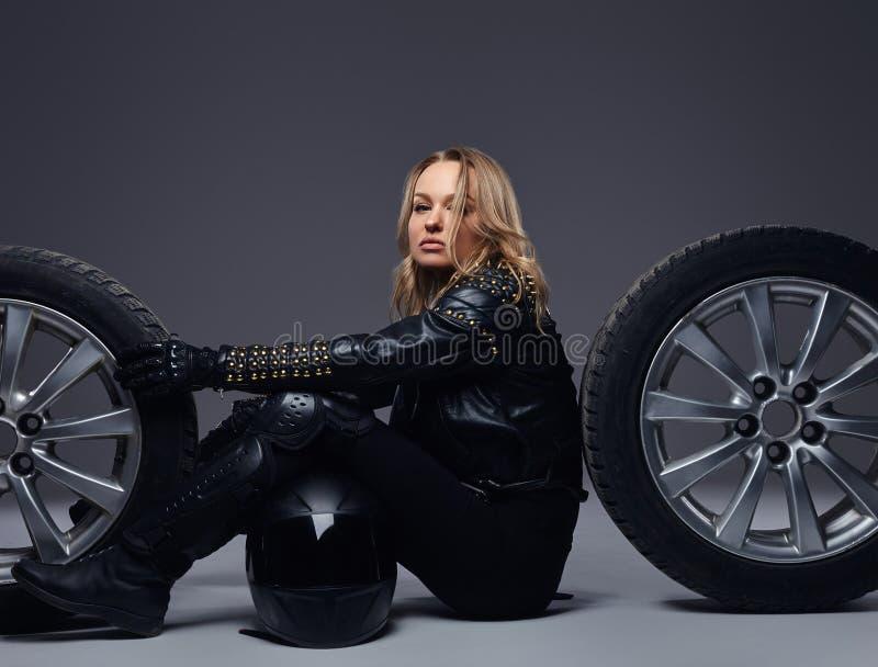 时尚,体育,极端 肉欲的骑自行车的人女孩佩带的摩托车齿轮坐与车轮的一个地板演播室 库存照片